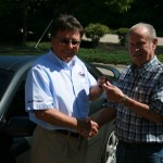Bruce King of King Collision Centers hands over the keys to a 2005 Mazda 6 to Ernie Menslage. Menslage's wife won the drawing for the auto, which was rebuilt by auto repair students from Plymouth South as part of the Plymouth Safe Driving Campaign.