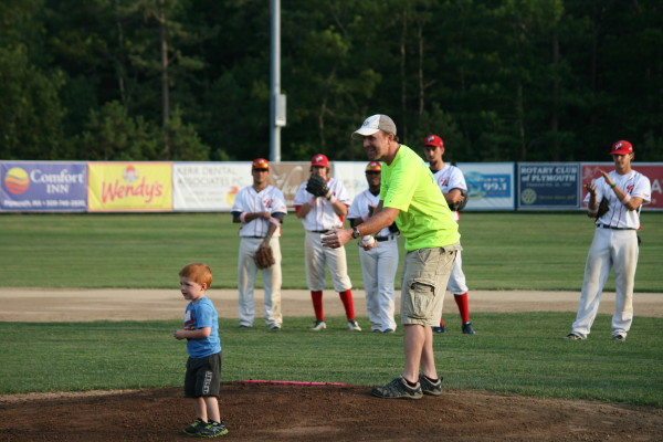 "Matt Romboldi and son Charlie throw out the first pitch for ""Pink"" night at the Plymouth Pilgrims baseball game to celebrate cancer research. Matt welcomes the community to participate in ""Run for Faith"" a family oriented road race to raise additional funds for cancer research and set for Sunday, August 11, 8:30 a.m. at Plimouth Plantation."